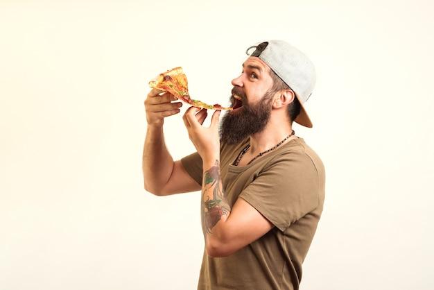 Glücklicher hungriger mann, der pizza isst