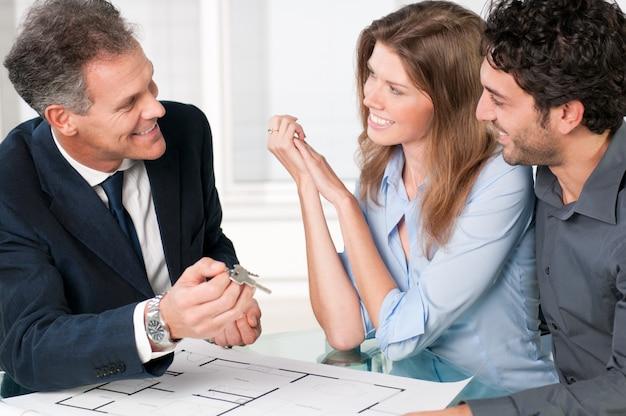 Glücklicher immobilienmakler, der einem jungen paar neue hausschlüssel zeigt