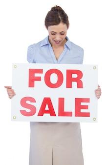 Glücklicher immobilienmakler, der mit für verkaufszeichen aufwirft