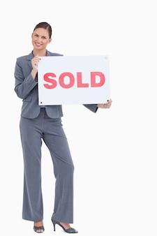 Glücklicher immobilienmakler mit verkaufszeichen