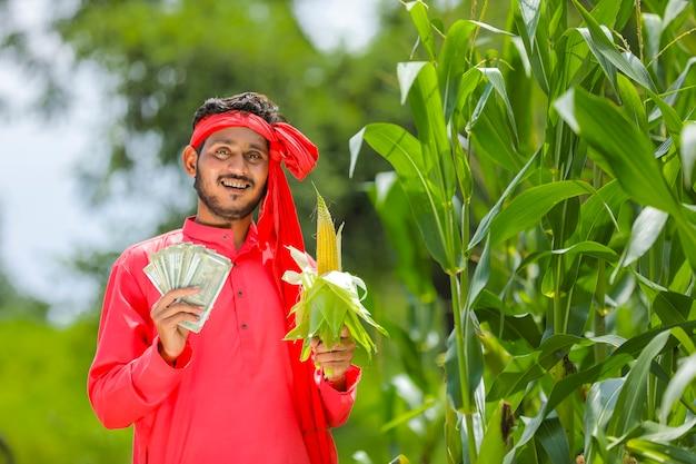 Glücklicher indischer bauer, der maisfrucht und indische währung am grünen maisfeld zeigt