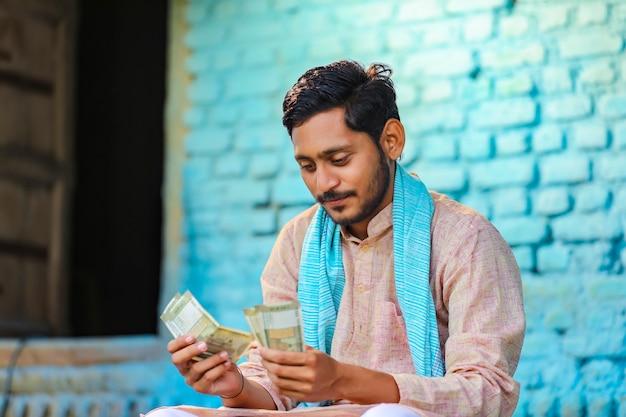 Glücklicher indischer bauer, der zu hause geld zählt.