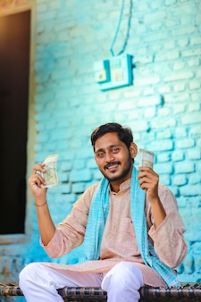 Glücklicher indischer bauer, der zu hause geld zeigt.