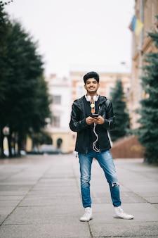 Glücklicher indischer mann, der geht und ein smartphone verwendet, um musik mit kopfhörern zu hören