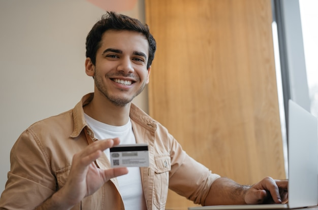 Glücklicher indischer mann, der kreditkarte hält und online auf der website einkauft