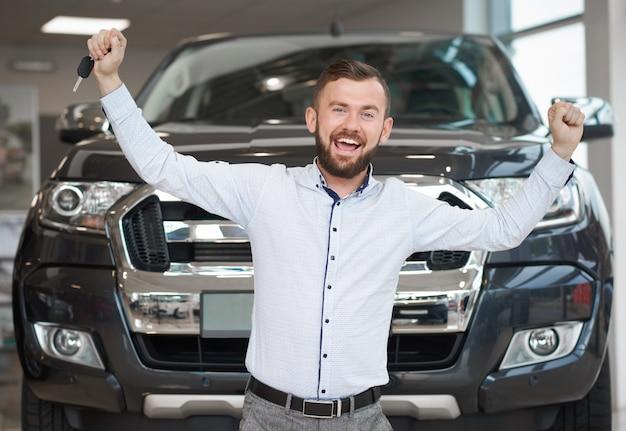 Glücklicher inhaber des neuen schwarzen jeeps, der hände lächelt und hochhält.