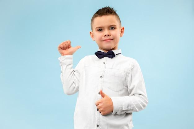 Glücklicher jugendlich junge, der lokalisiert auf blauem studiohintergrund lächelt. schönes männliches halblanges porträt. junges emotionales kind, das nach links zeigt. die menschlichen emotionen, gesichtsausdruck konzept