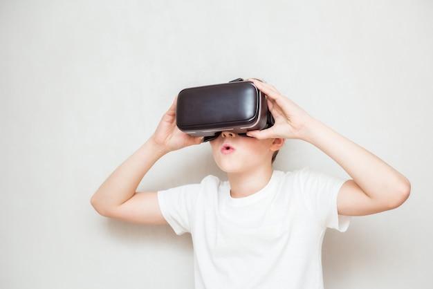 Glücklicher jugendlich junge, der virtual-reality-schutzbrillen trägt, die filme ansehen oder videospiele spielen, lokalisiert auf weiß. fröhlicher teenager, der in vr-brille schaut. lustiges kind, das 3d-gadget-technologie erlebt