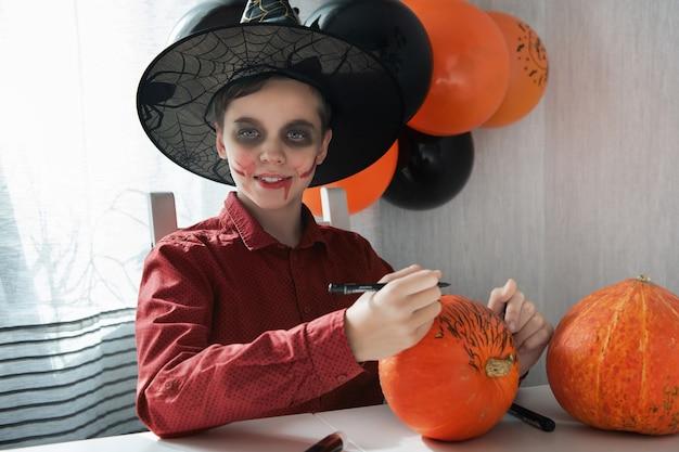 Glücklicher jugendlich junge im kostüm, das sich auf die halloween-feier vorbereitet, die einen kürbis zeichnet