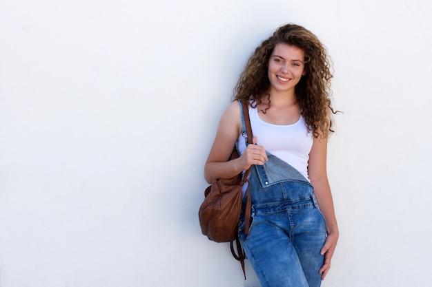 Glücklicher jugendlich student mit dem rucksack getrennt auf weiß