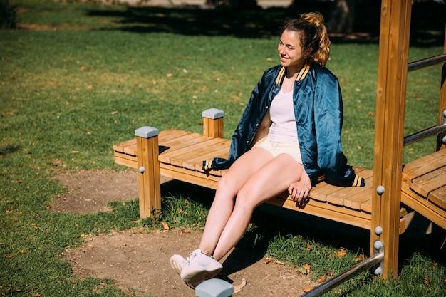 Glücklicher jugendlicher, der auf bank im park sitzt