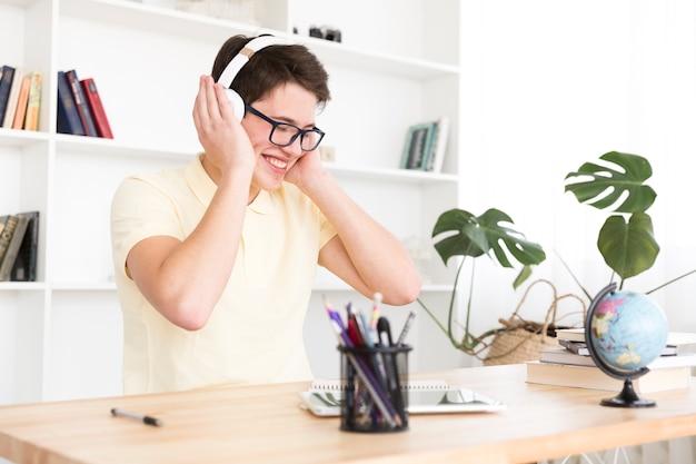 Glücklicher jugendlicher, der musik hört