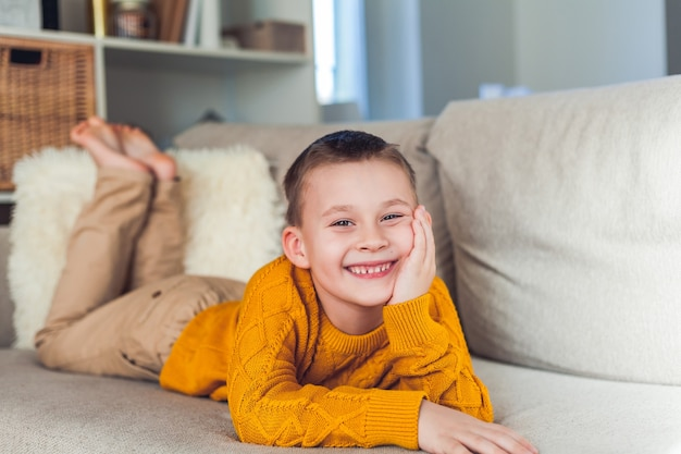 Glücklicher junge 6 jahre alt ruht auf dem sofa.