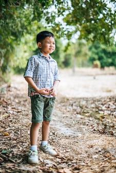 Glücklicher junge, der alleine im park spielt