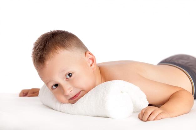 Glücklicher junge, der auf einem massagetisch liegt und auf massage wartet