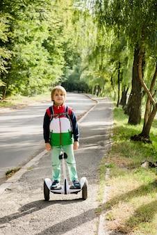 Glücklicher junge, der auf elektrischem hoverboard am sonnigen herbstpark balanciert