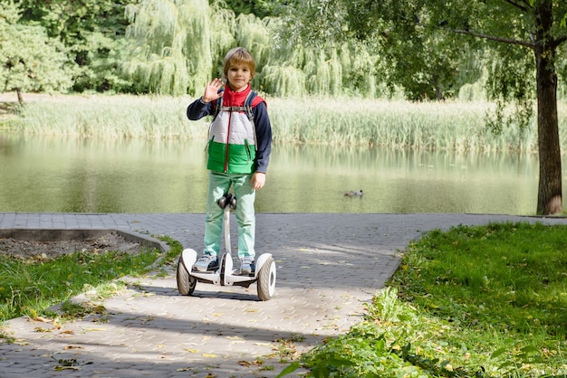 Glücklicher junge, der auf elektrischem hoverboard am sonnigen park balanciert