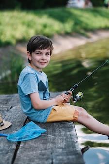Glücklicher junge, der auf hölzernem pier über dem see hält angelrute sitzt