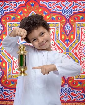 Glücklicher junge, der auf ramadan laterne zeigt