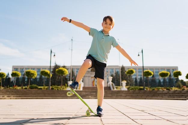 Glücklicher junge, der auf skateboard im park spielt, kaukasisches kind, das penny board reitet, skateboard übend.