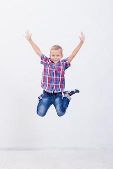 Glücklicher junge, der auf weiß springt