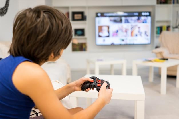 Glücklicher junge, der computerspiele auf großem bildschirm spielt