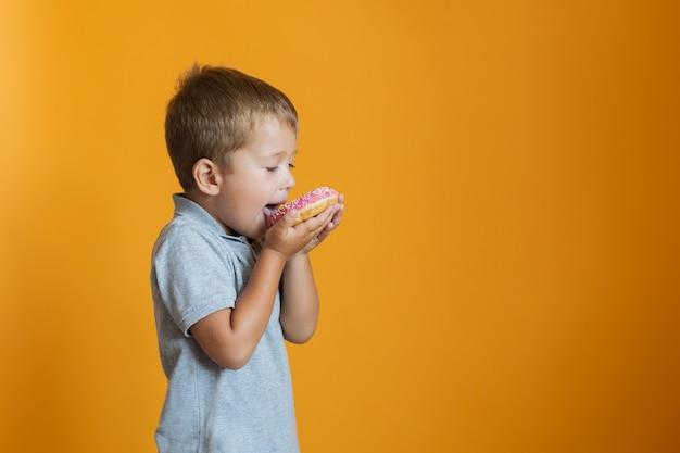 Glücklicher junge, der donut auf orange wand isst
