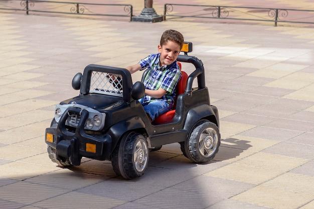 Glücklicher junge, der ein spielzeugauto fährt
