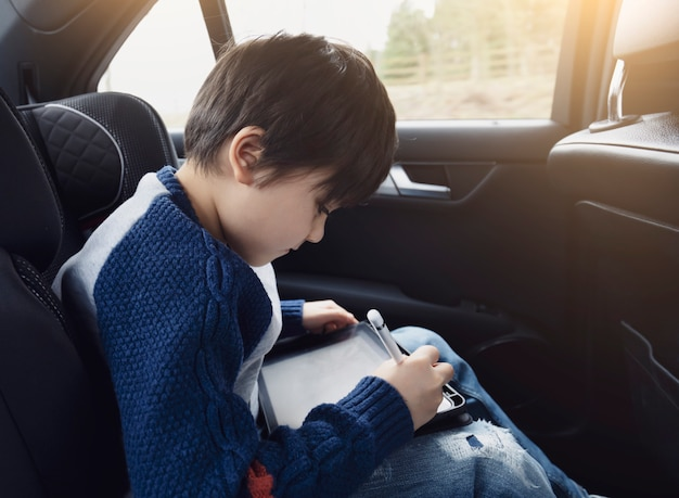 Glücklicher junge, der einen tablet-computer verwendet, während er auf dem hinteren beifahrersitz eines autos mit einem sicherheitsgurt sitzt, kinderjunge, der auf smartpad zeichnet, porträt des kleinkindes, das ihn selbst auf einem roadtrip unterhält.