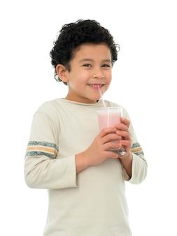 Glücklicher junge, der erdbeermilch-shake trinkt