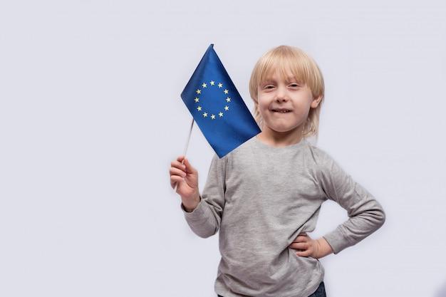 Glücklicher junge, der flagge der europäischen union hält. reisen mit kindern in europa