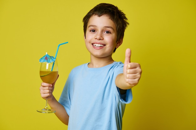 Glücklicher junge, der glas mit köstlichem fruchtgetränk hält, verziert mit cocktailregenschirm und zeigt daumen oben auf gelb mit kopienraum.
