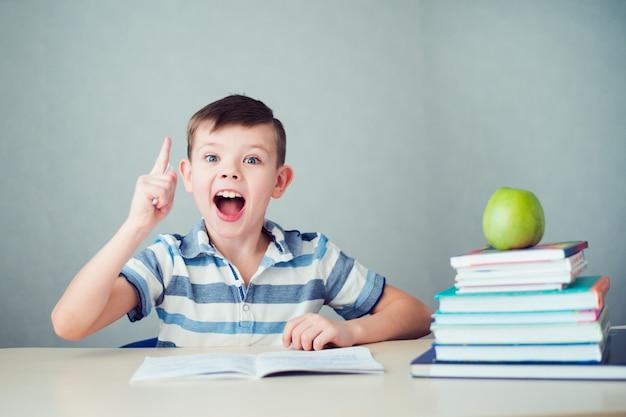 Glücklicher junge, der hausaufgaben macht und gute idee findet