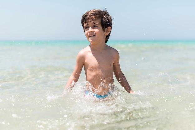 Glücklicher junge, der im wasser an der küste spielt