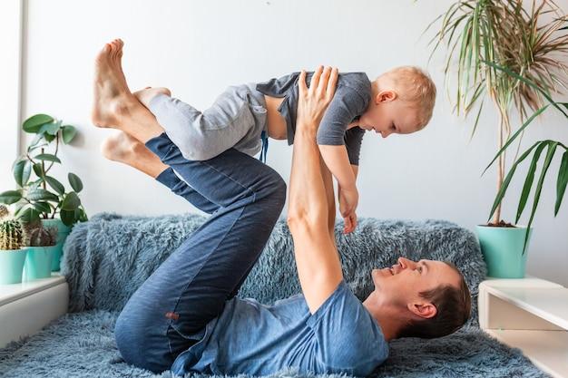 Glücklicher junge, der in den armen des vaters fliegend schaut, liebender familienvater hält, der niedlichen kleinen kindersohn hält, der flugzeug spielt, bindung, spaß auf der couch hat