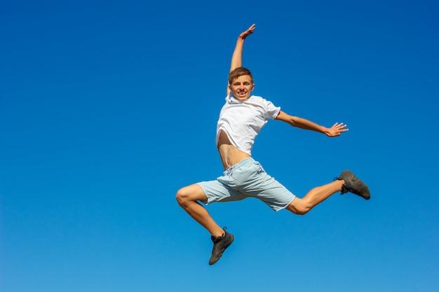 Glücklicher junge, der in den blauen himmel springt