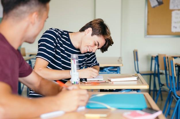Glücklicher junge, der in der klasse schreibt