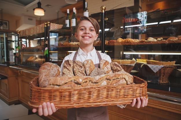 Glücklicher junge, der korb voll frisches brot hält und seinen eltern in der familienbäckerei hilft