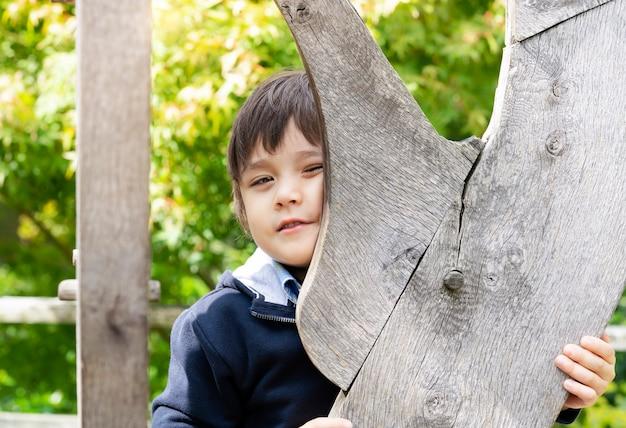 Glücklicher junge, der lustiges gesicht beim spielen des versteckens am park bildet,