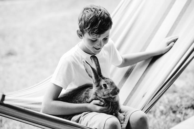 Glücklicher junge, der mit kaninchen in der hängematte sitzt