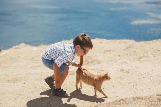 Glücklicher junge, der mit roter katze spielt.