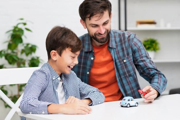 Glücklicher junge, der mit spielzeugautos mit seinem vati spielt