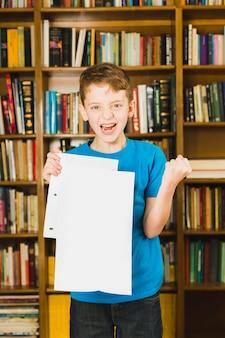 Glücklicher junge, der papier mit ausgezeichnetem kennzeichen zeigt