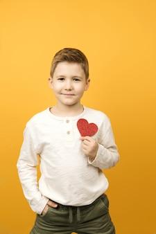 Glücklicher junge, der rote herzform lokalisiert hält. st. valentinstag konzept.