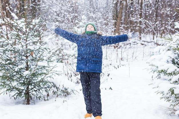 Glücklicher junge, der schnee wirft. kinder-, saison- und winterkonzept.