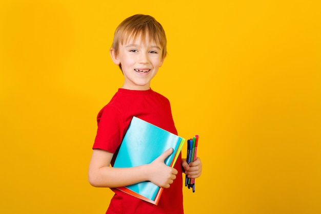 Glücklicher junge, der schulmaterial über gelbem hintergrund hält. kind mit notizbüchern und stiften. zurück zum schulkonzept