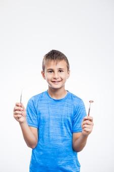 Glücklicher junge, der skalator und zahnmedizinischen spiegel auf weißem hintergrund hält