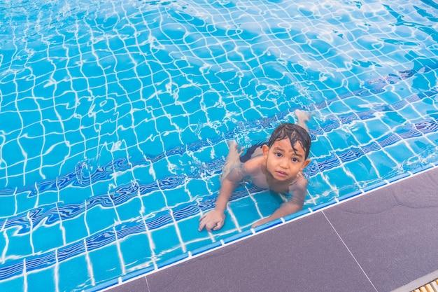 Glücklicher junge, der um swimmingpool und das schauen sitzt