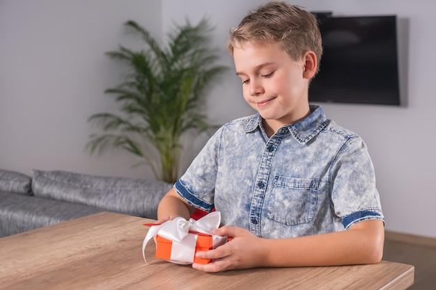 Glücklicher junge, der verpacktes geschenk und karte für muttertag oder valentinstag hält und betrachtet.