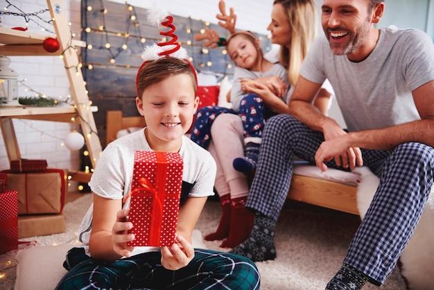 Glücklicher junge, der weihnachtsgeschenk hält
